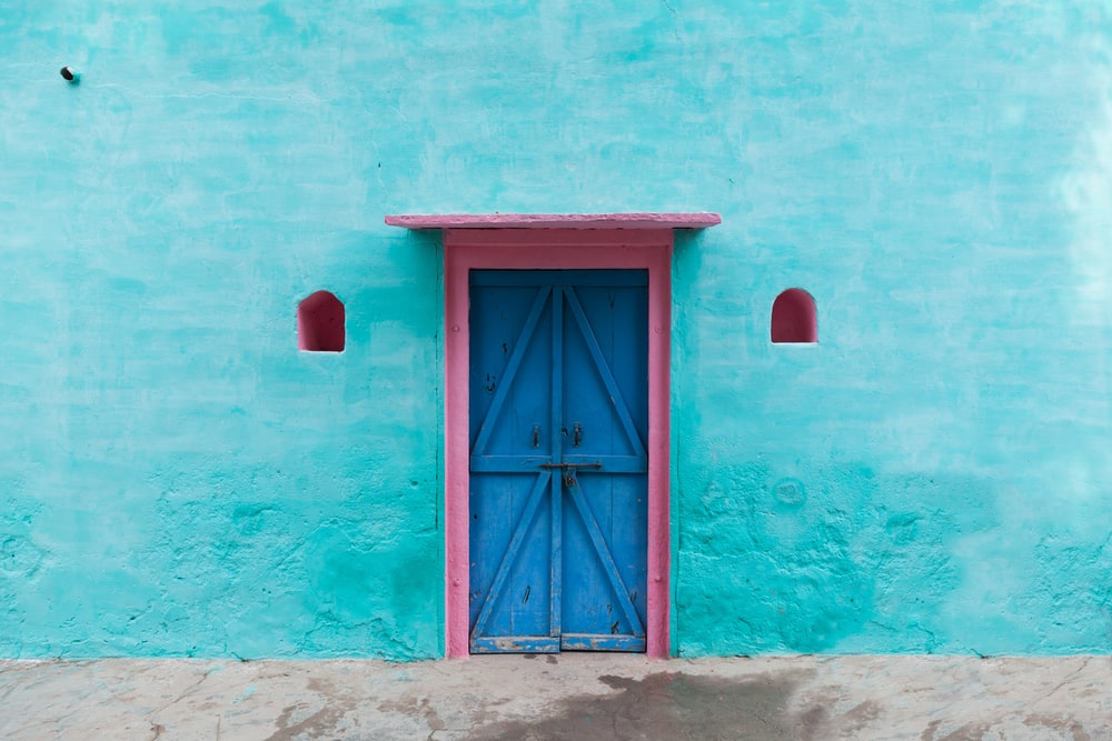 red wooden door on blue concrete wall