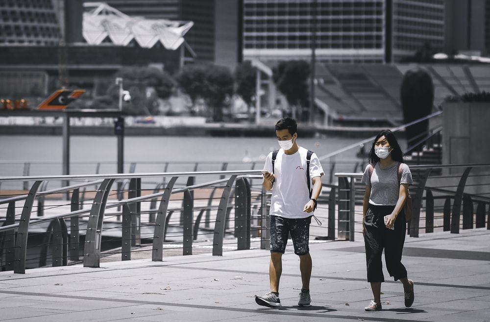 man in white crew neck t-shirt and black shorts standing beside woman in black tank
