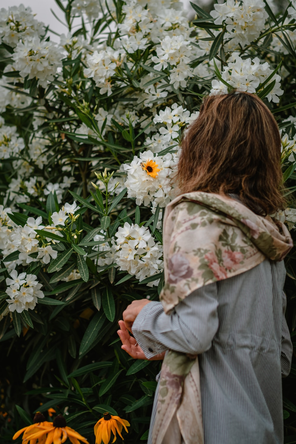 woman in gray jacket holding white flowers