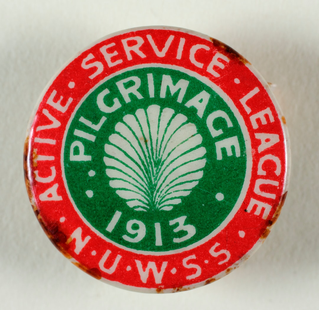 Suffrage Campaigning: National Union of Women's Suffrage Societies [NUWSS] 1913 Badge, metal, paper, plastic, round, produced by the National Union of Women's Suffrage Societies, green circle in the centre with a white shell motif and inscription: 'Pilgrimage 1913', red and white border with a white inscription: 'Active Service League NUWSS'. TWL.2004.589.3