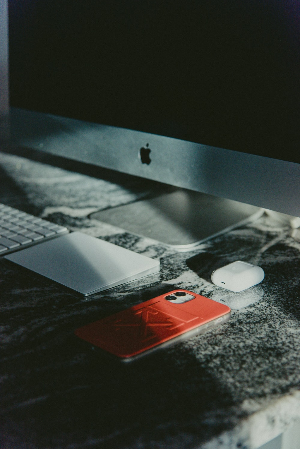 white and red iphone case on black table