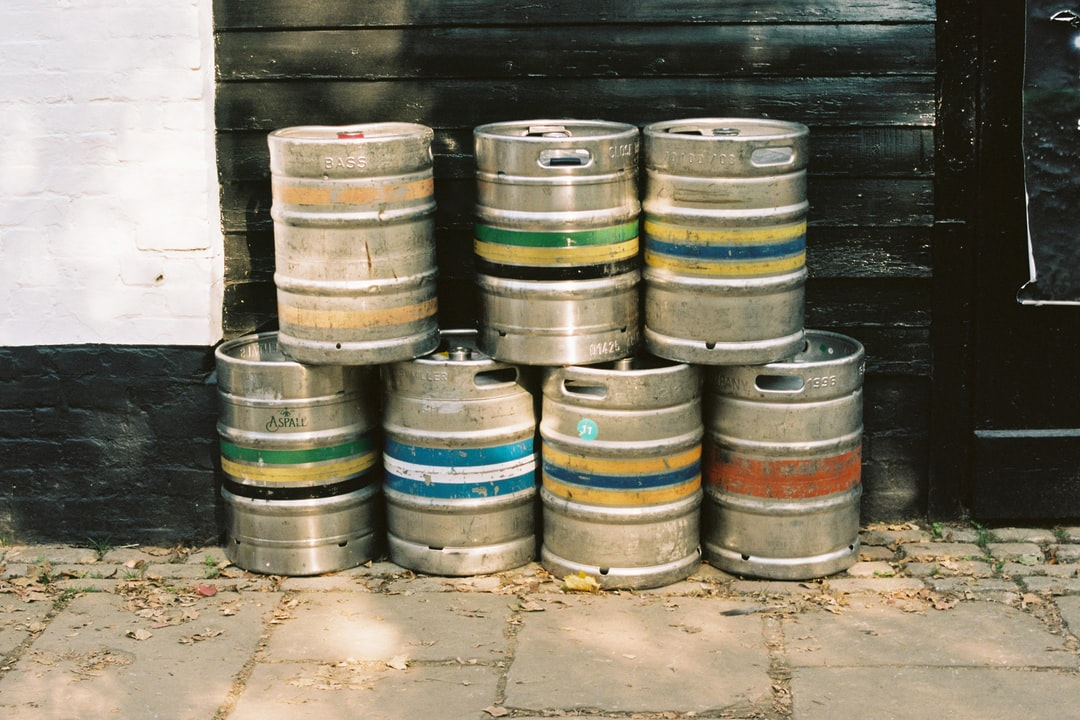 Different coloured striped beer barrels or kegs outside a pub in England. Shot on film.