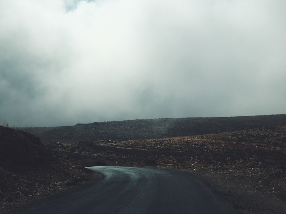 gray asphalt road under white clouds