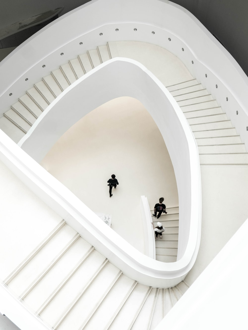 people walking on white spiral staircase