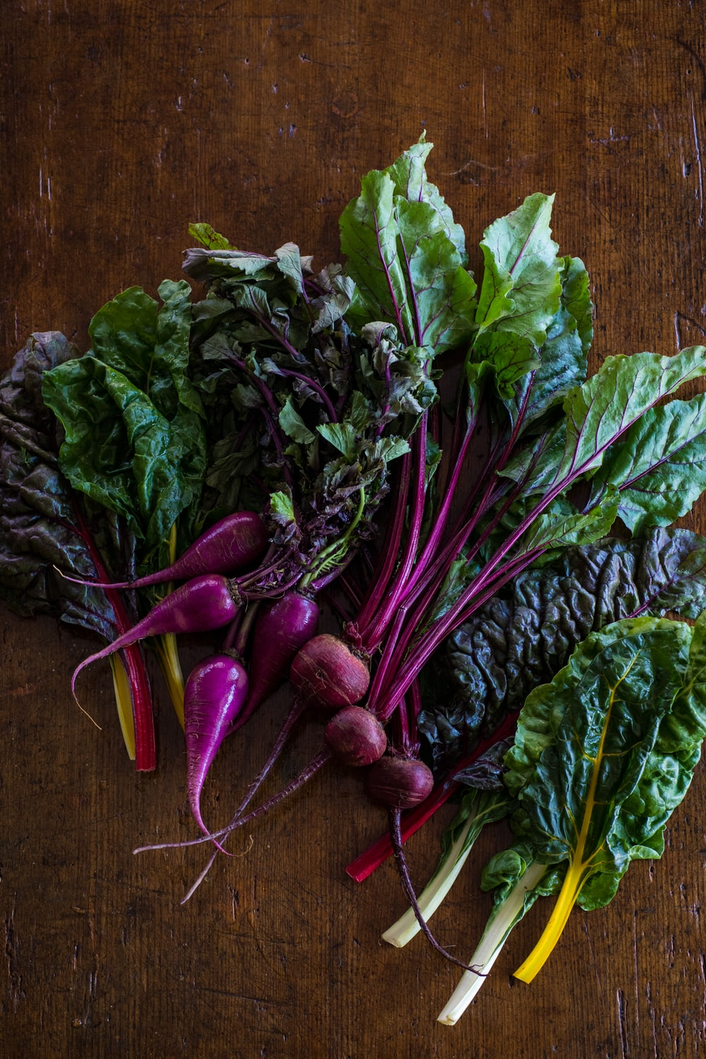 green and purple vegetable on brown wooden table