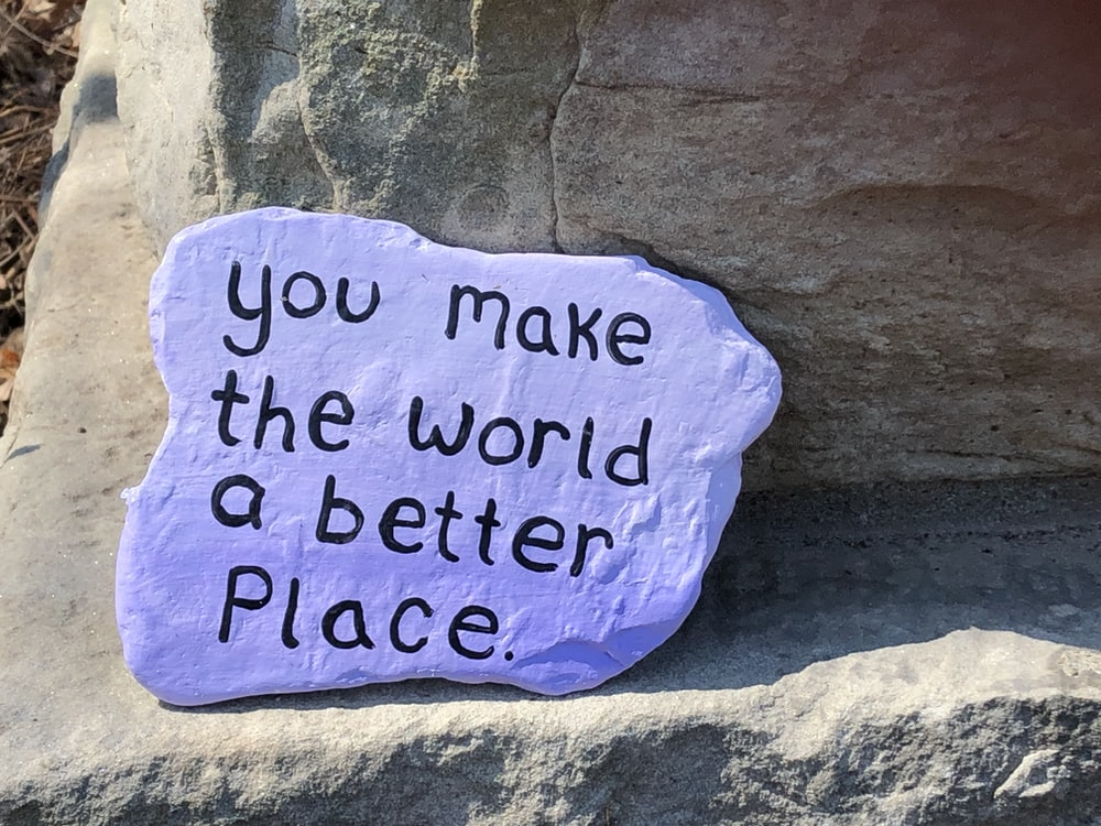 blue and black quote on brown rock
