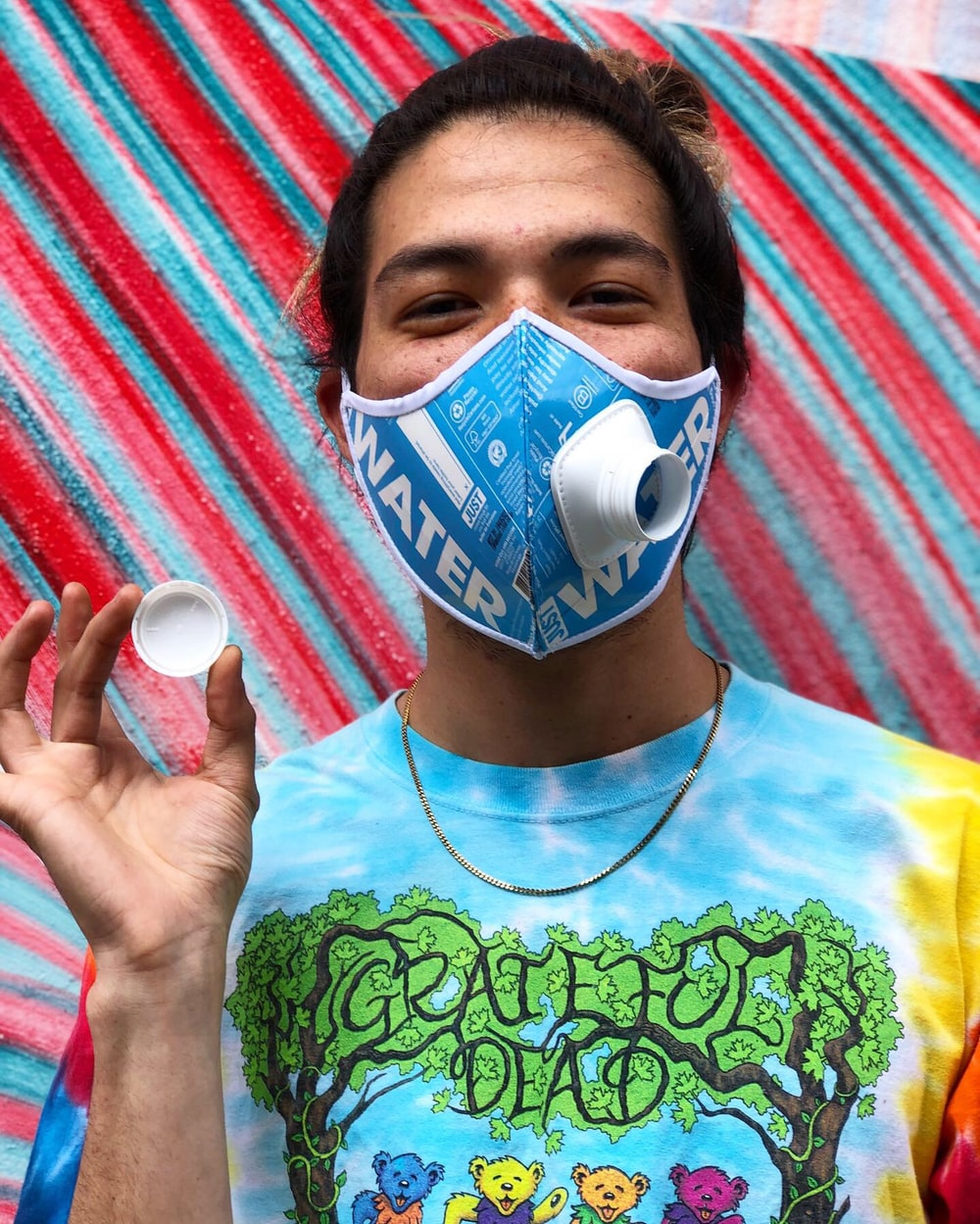 boy in green crew neck shirt with blue mask