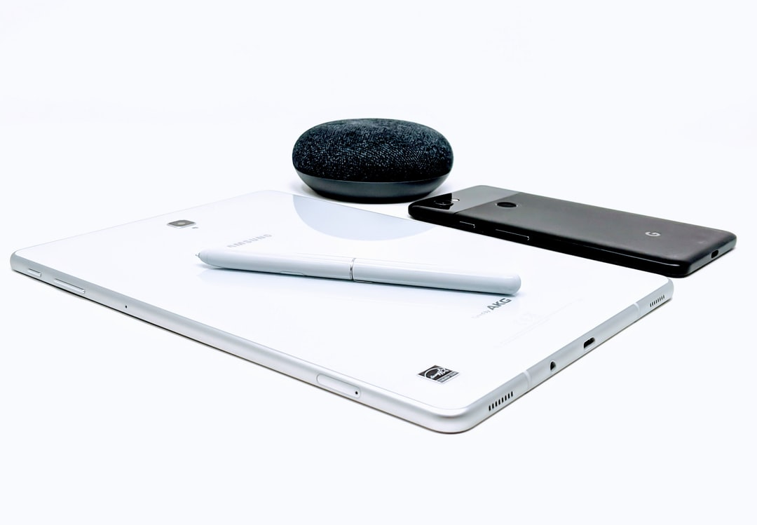 A Samsung Galaxy Tablet with S-Pen Stylus, Google Home, and Google Pixel rest on a white table in a home office.