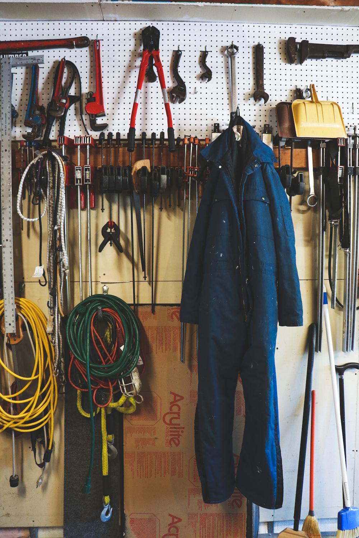 black leather jacket hanging on brown wooden drawer