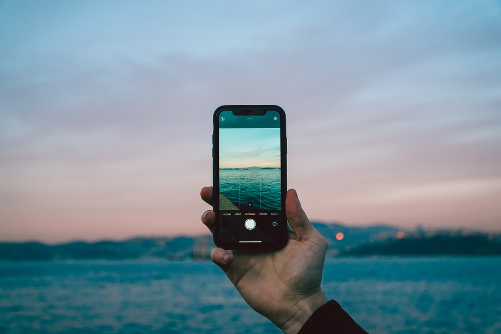 person holding iphone 6 taking photo of sea during daytime