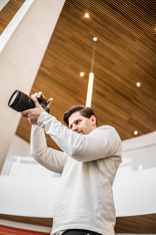 man in white long sleeve shirt holding black camera