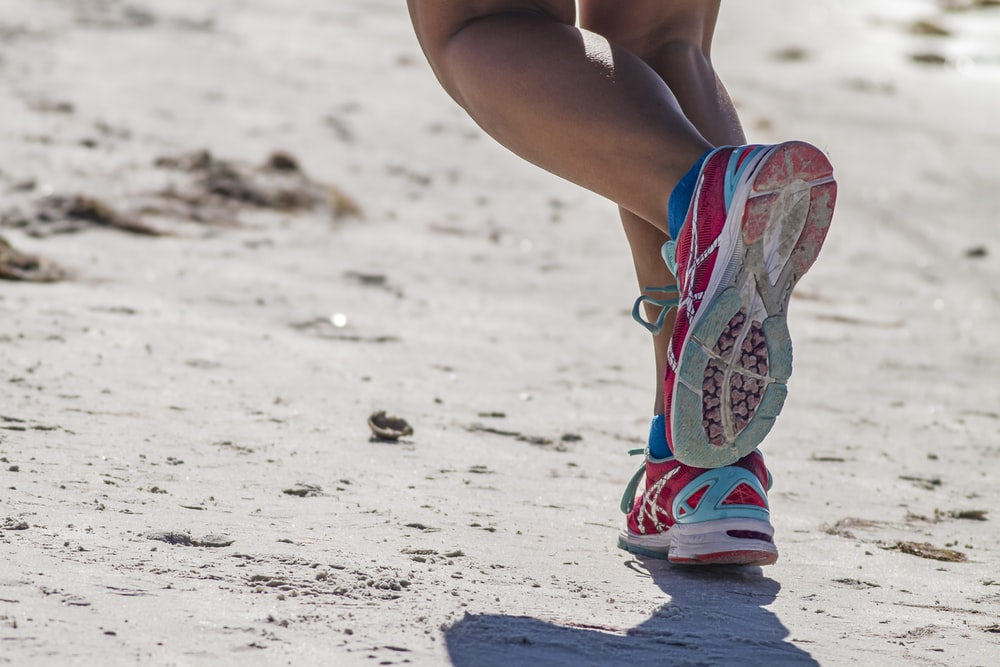 woman in white red and blue sneakers sitting on white sand during daytime