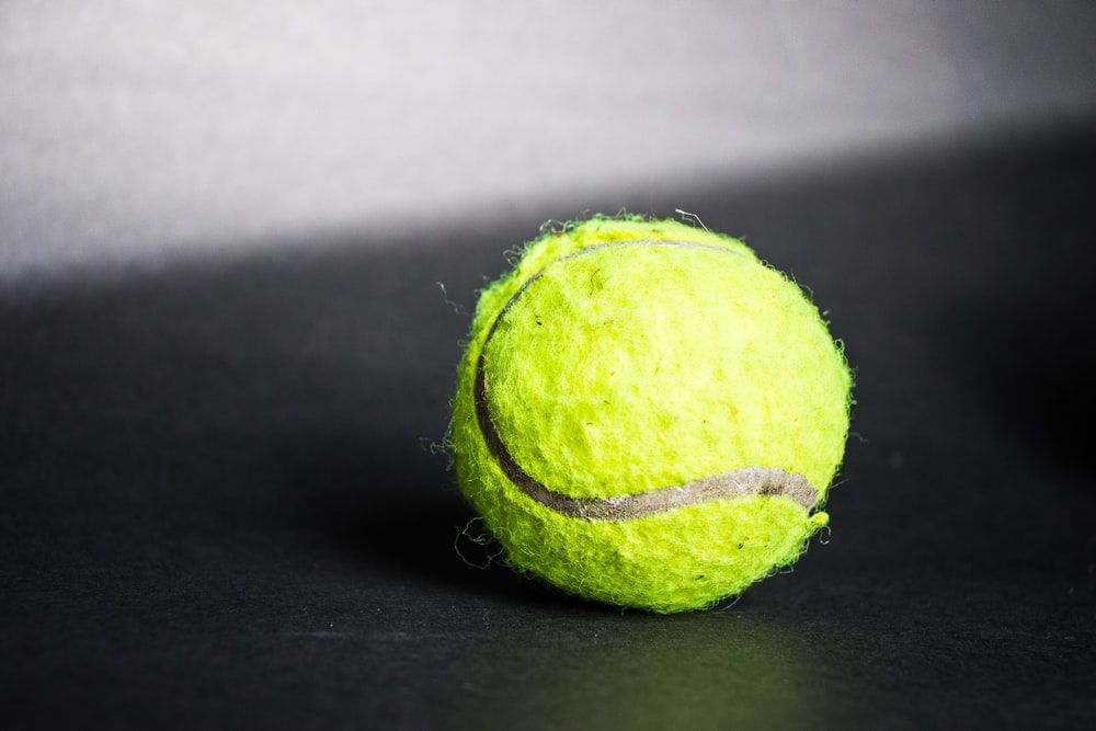 green tennis ball on black textile
