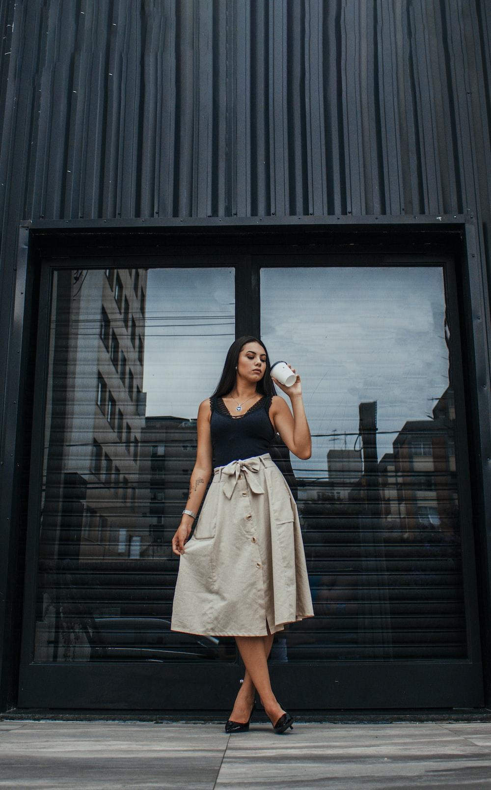 woman in beige sleeveless dress standing beside black wooden door