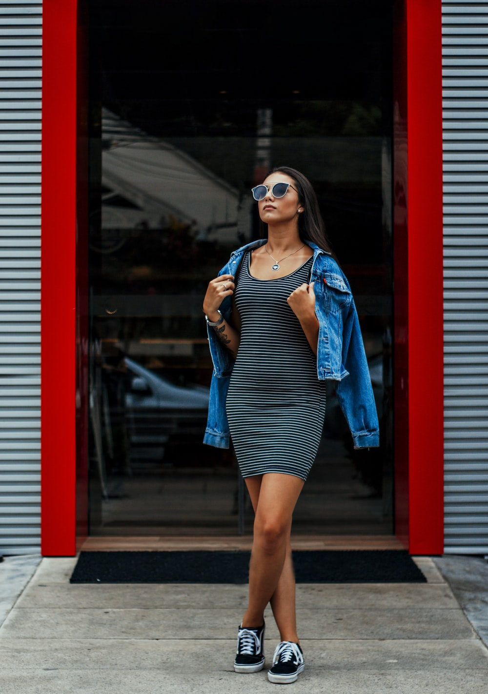 woman in blue and white stripe tank top and blue denim jacket standing beside red wall