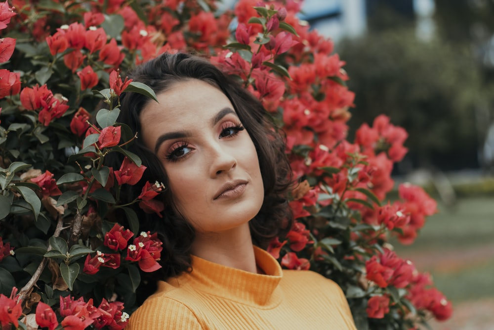 woman in yellow turtleneck shirt standing beside red flowers