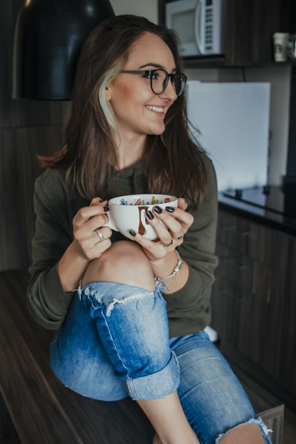 woman in brown long sleeve shirt and blue denim jeans holding white ceramic mug