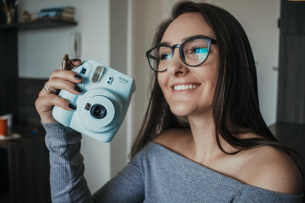 woman in gray off shoulder shirt holding gray and black camera