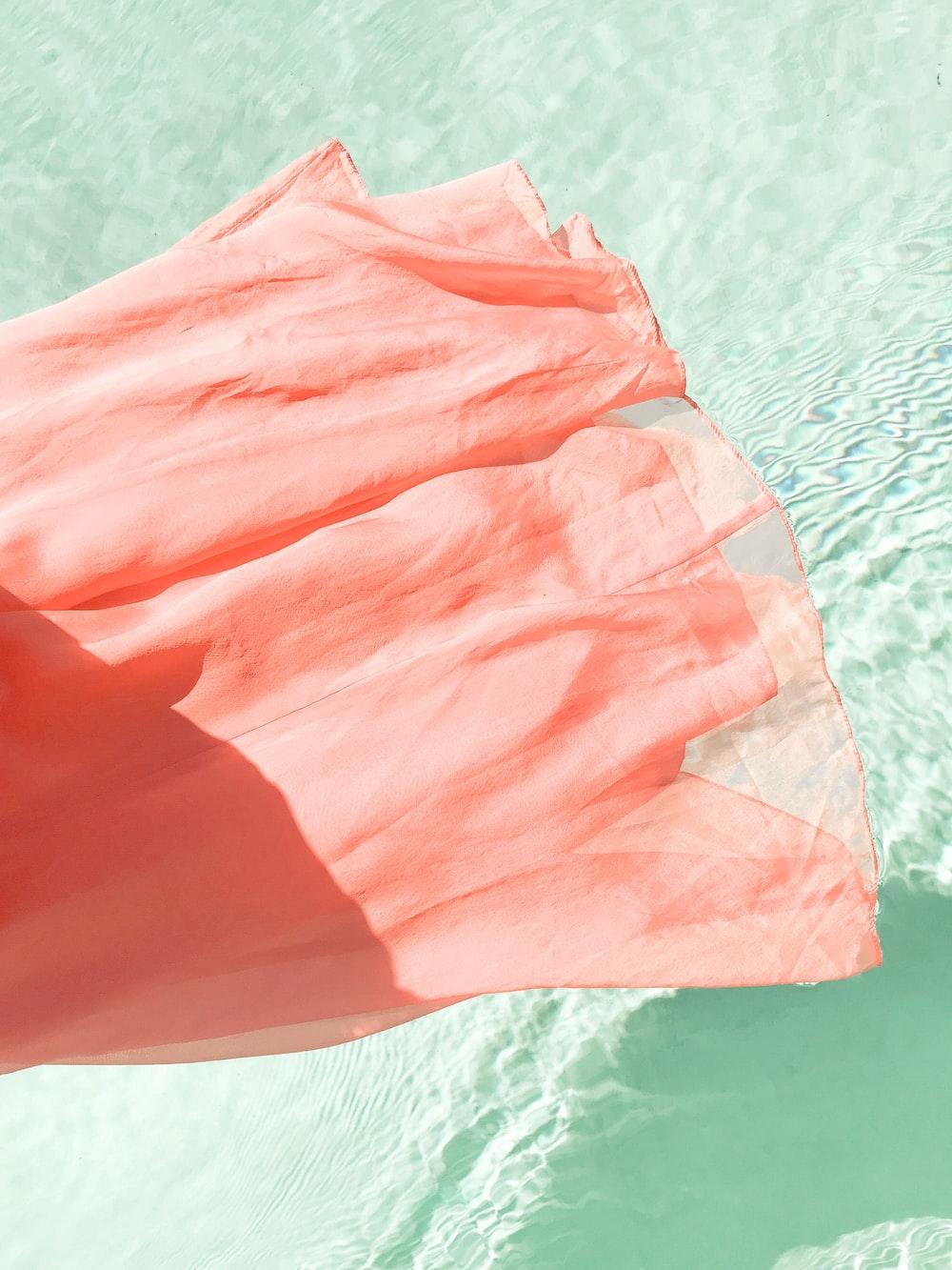 pink textile on white sand