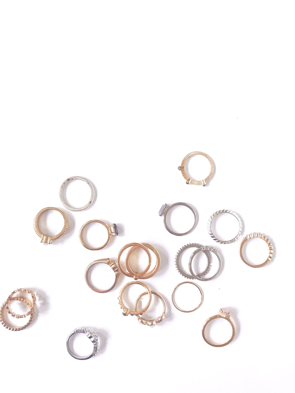 silver and gold rings on white surface
