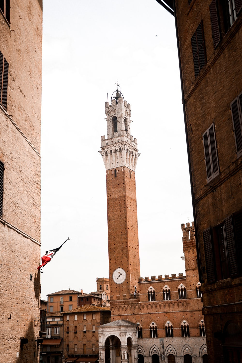 brown concrete tower with red flag on top