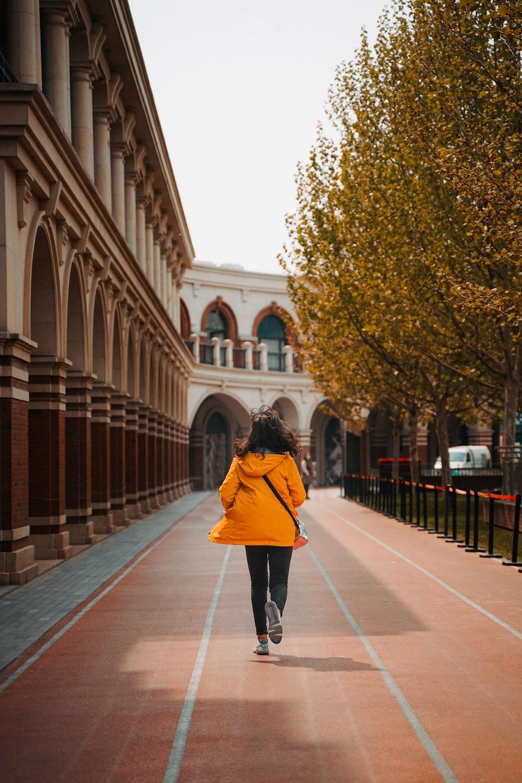 woman in red coat walking on sidewalk during daytime
