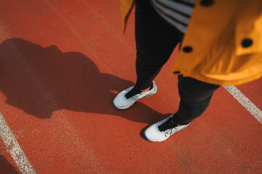 person in black pants and white nike sneakers