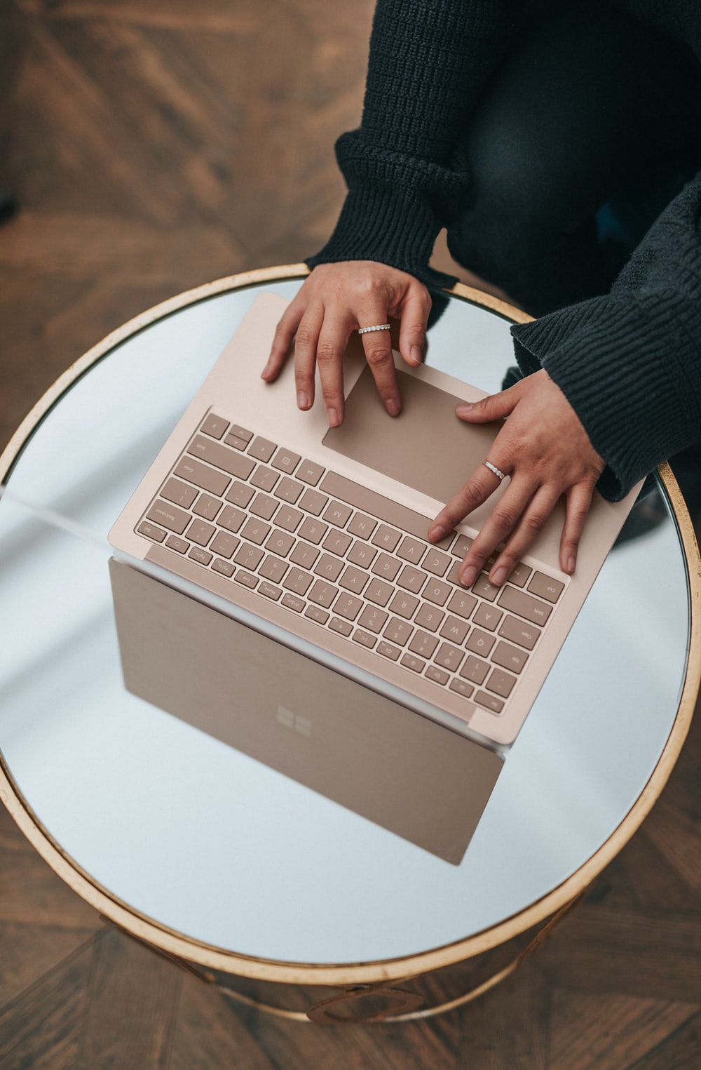 person using Microsoft Surface Laptop on white round table