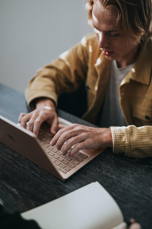 man in yellow dress shirt using Microsoft Surface Laptop