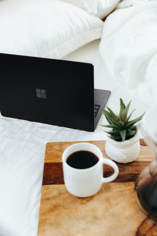 black microsoft surface laptop beside white ceramic mug on white bed