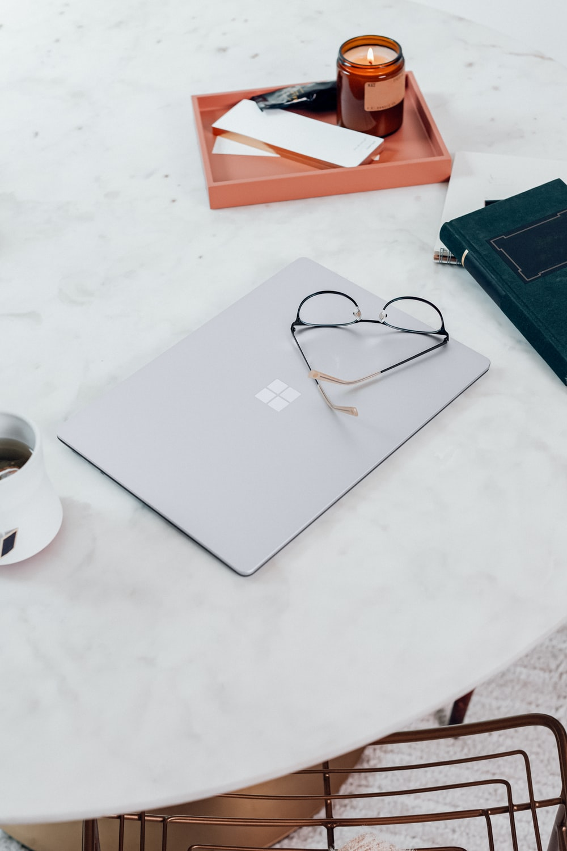 silver Microsoft Surface Laptop 3 in Platinum  beside black framed eyeglasses on white table