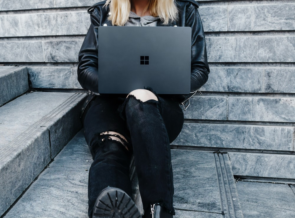 woman in black jacket and black pants sitting on concrete stairs usingMicrosoft Surface Laptop