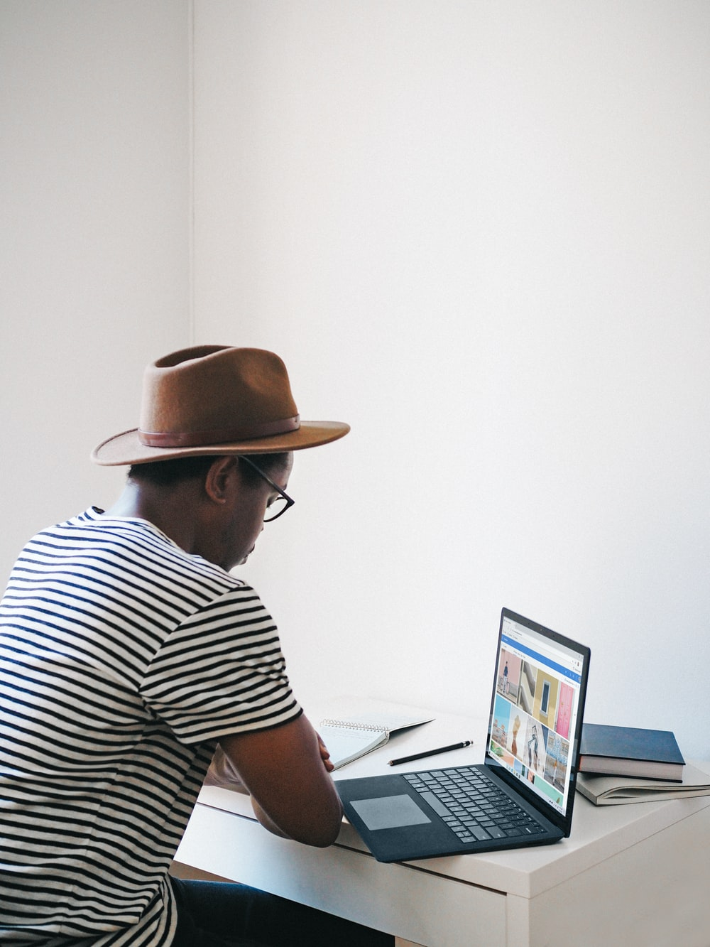 man in white and black stripe shirt wearing brown hat sitting on chair using a Microsoft surface cobalt laptop