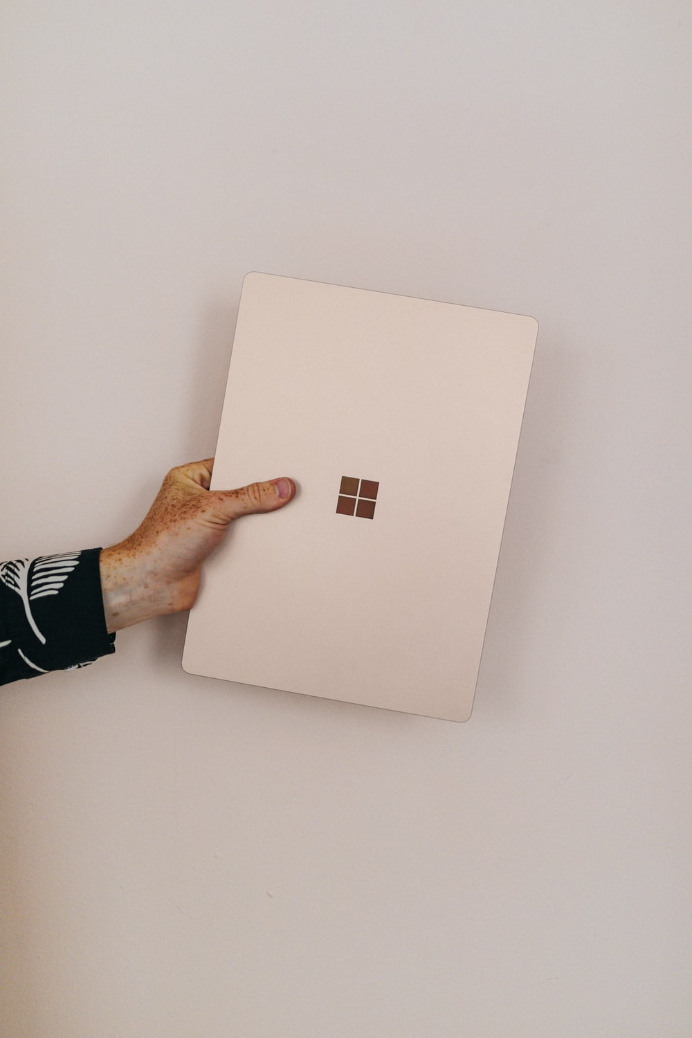 person holding sandstone microsoft Surface laptop laptop