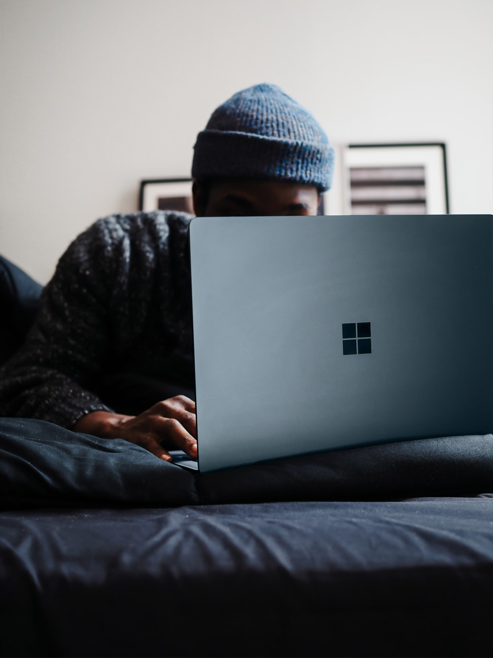 person in gray knit cap using microsoft surface computer in cobalt blue colour