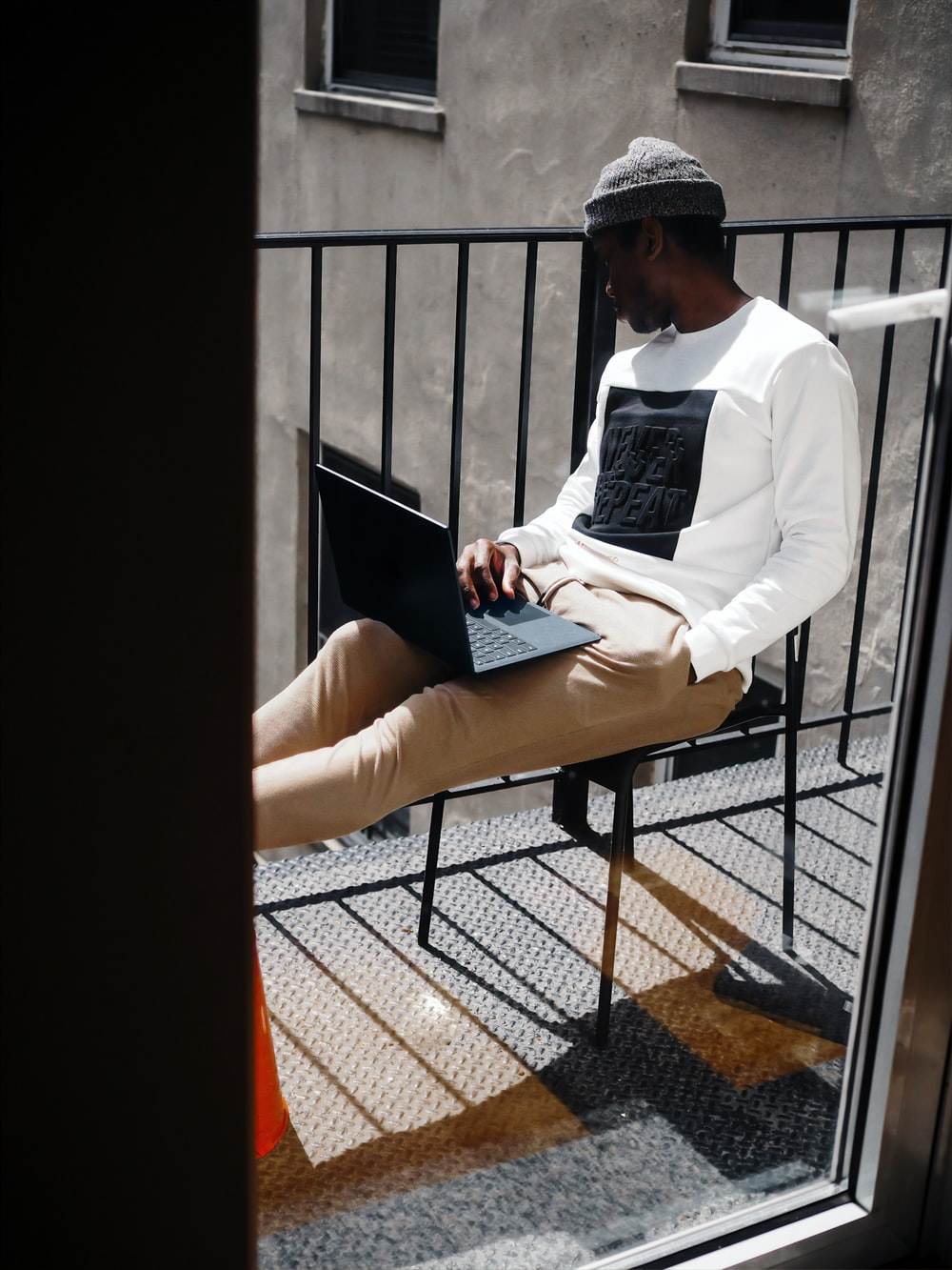 man in white shirt sitting on his balcony working on a cobalt blue microsoft surface laptop