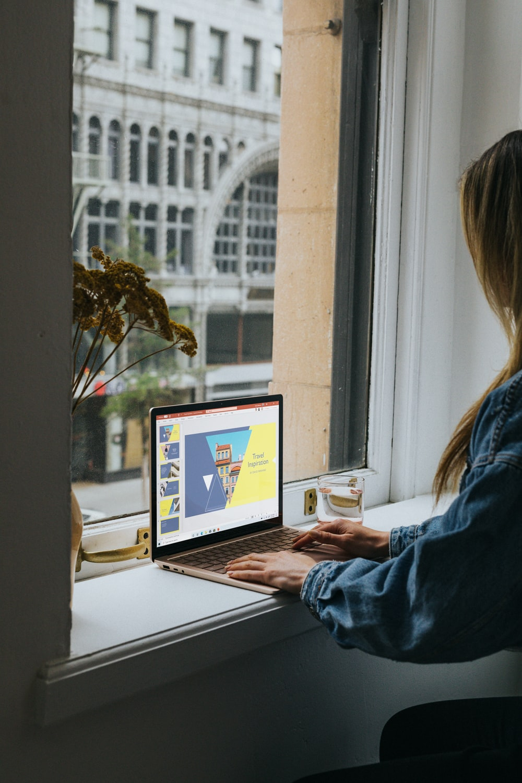 woman in blue denim jacket using Surface 3 Laptop