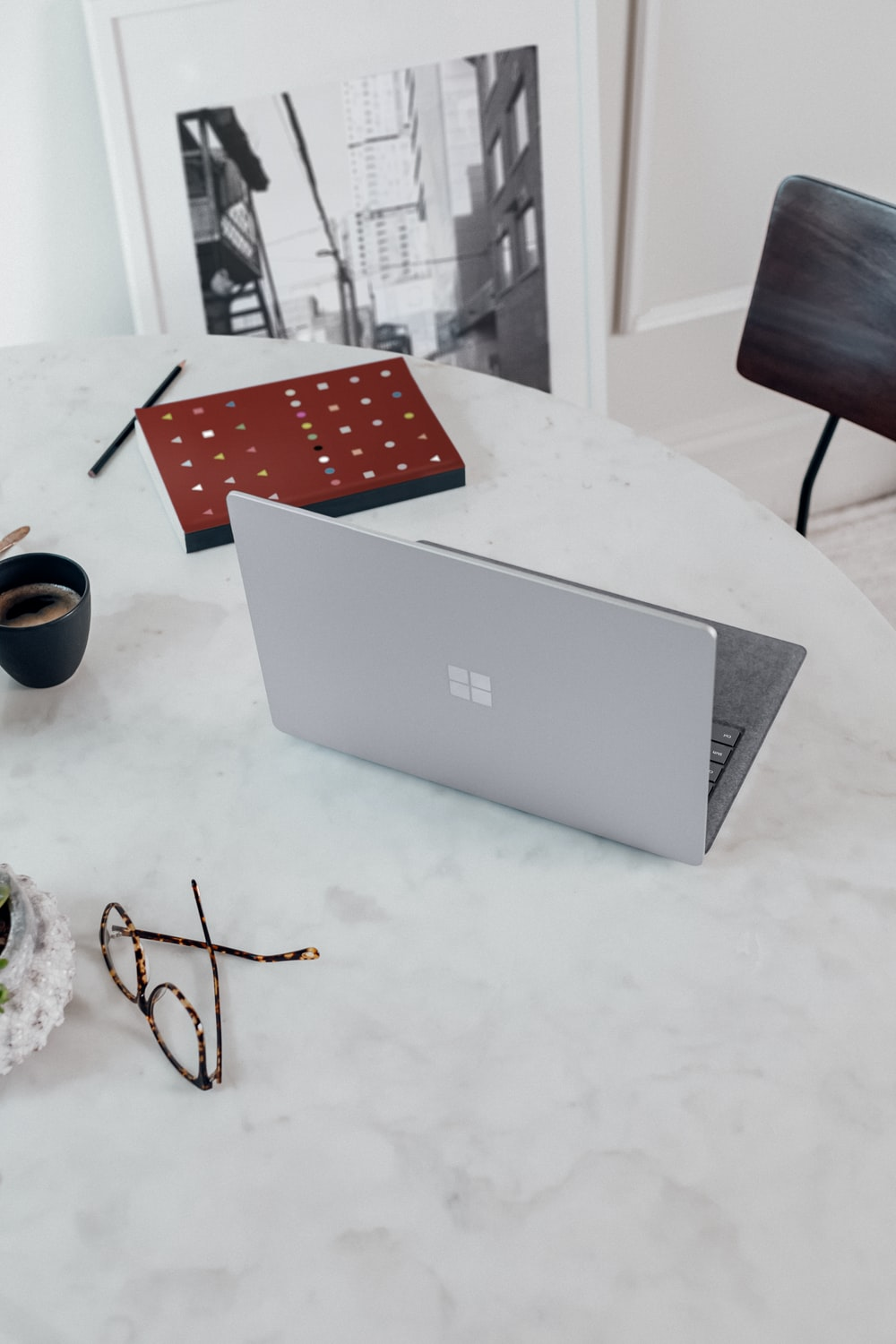 silver microsoft surface laptop computer on white table