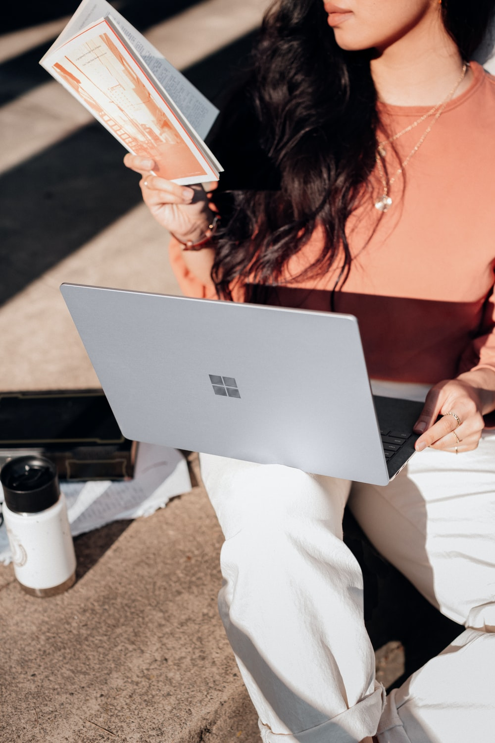 woman in orange shirt and white pants holding silver microsoft surface laptop computer