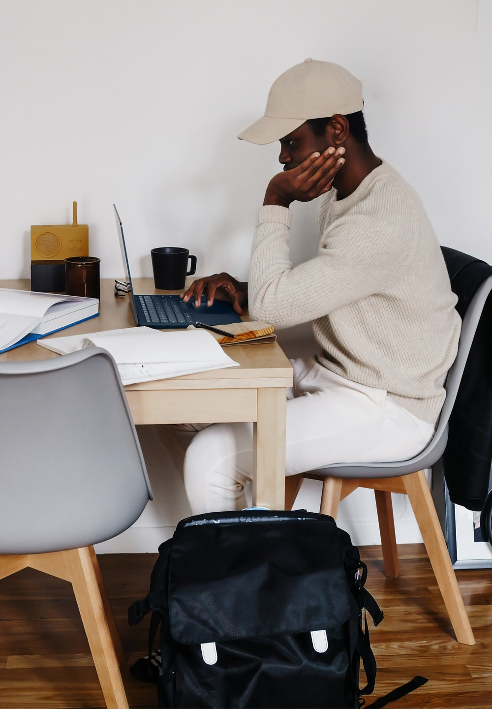 man in white sweater sitting on chair using Microsoft Surface Laptop 3