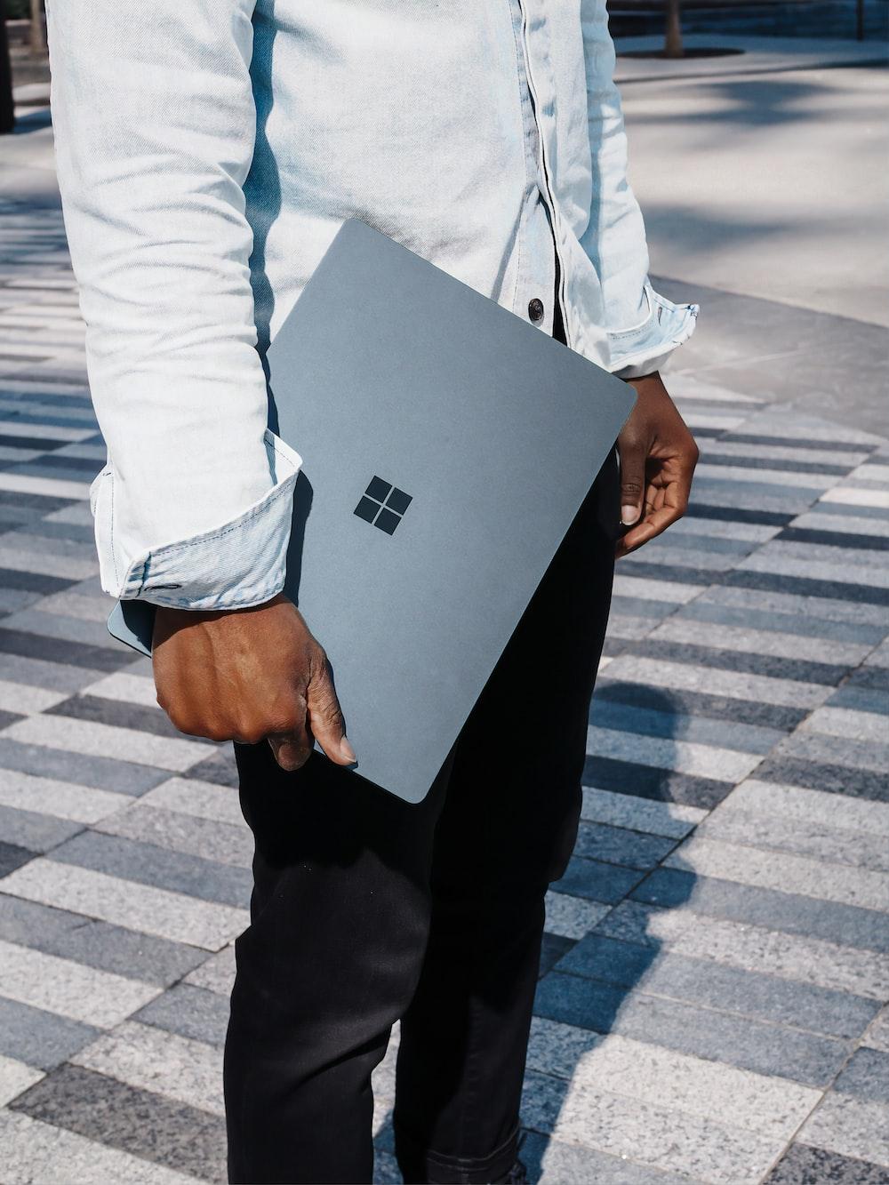man in dress shirt holding blue microsoft surface laptop computer