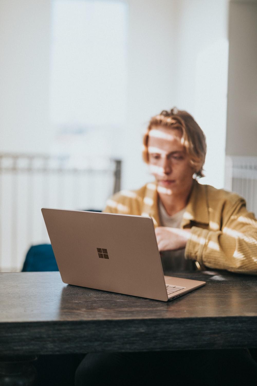 man in yellow jacket using microsoft surface laptop