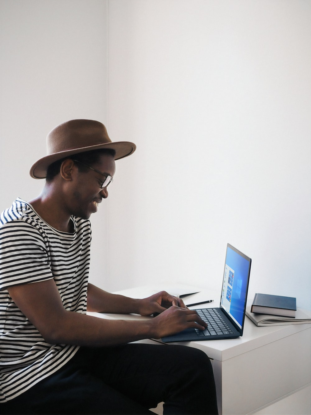 man in white and black striped shirt using microsoft surface cobalt blue laptop computer