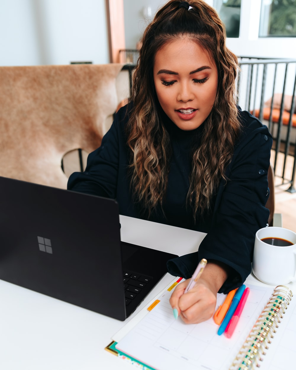 woman in black sweater with a black microsoft surface laptop on a table