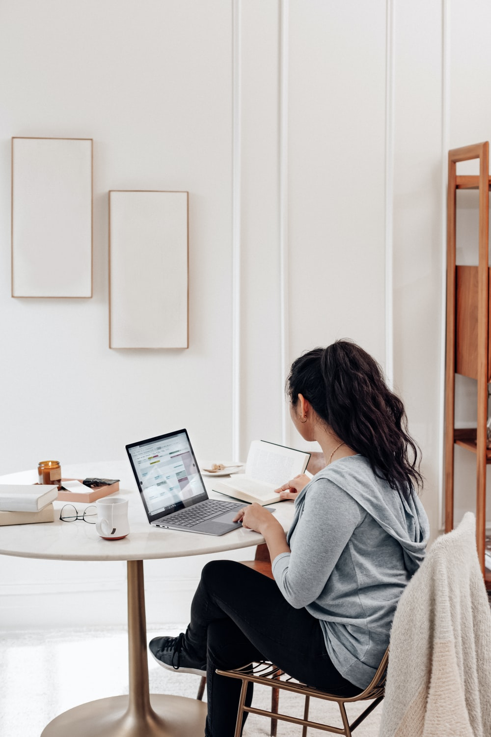 woman in gray sweater using microsoft surface laptop