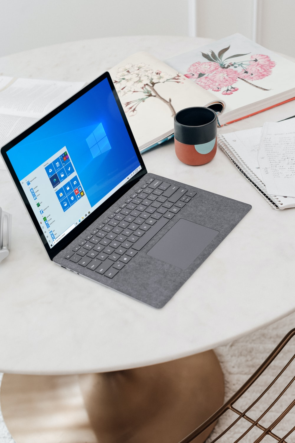 gray microsoft surface laptop computer on white table
