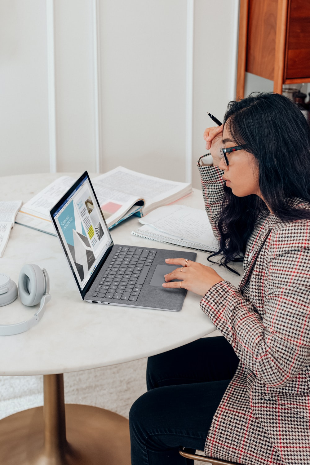 woman in red and white plaid dress shirt using microsoft surface laptop