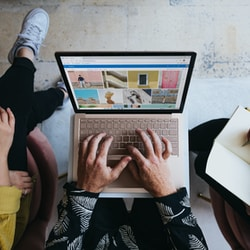 person using microsoft surface laptop on lap with two other people