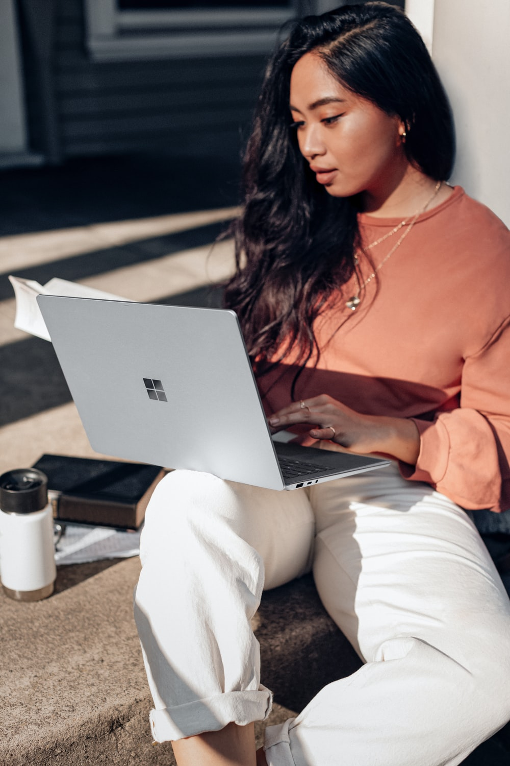 woman in orange long sleeve shirt and white pants sitting on floor using Surface Laptop