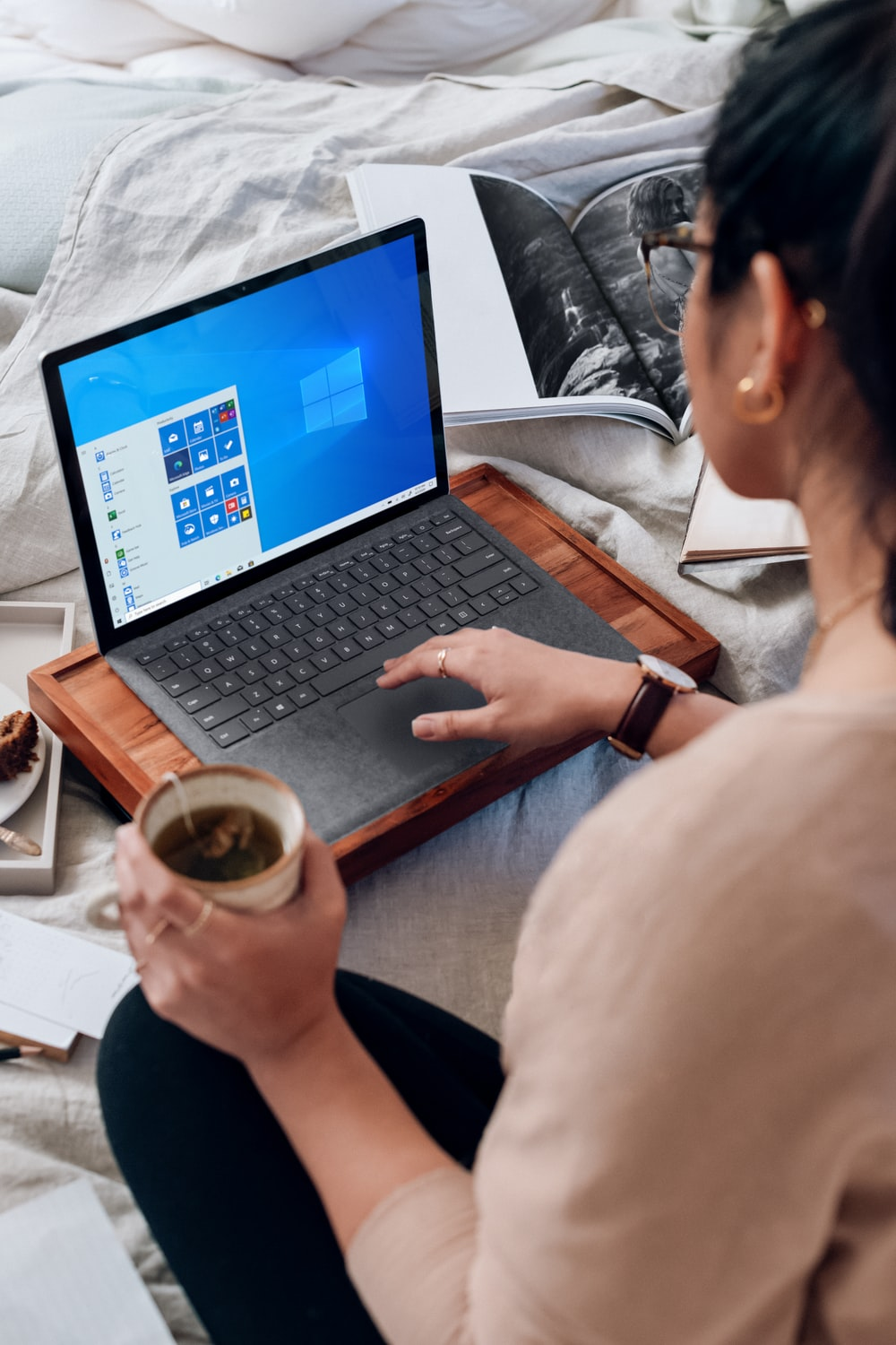 woman in white long sleeve shirt using Microsoft Surface Laptop